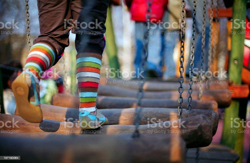 Girl is running through the wooden bridge on children playground royalty-free stock photo
