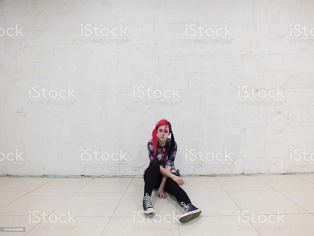 girl is sitting against a white wall stock photo