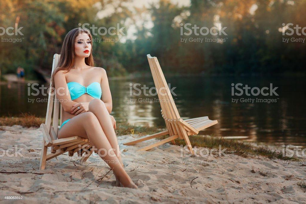 Girl is sitting deck chair beach near the lake. stock photo