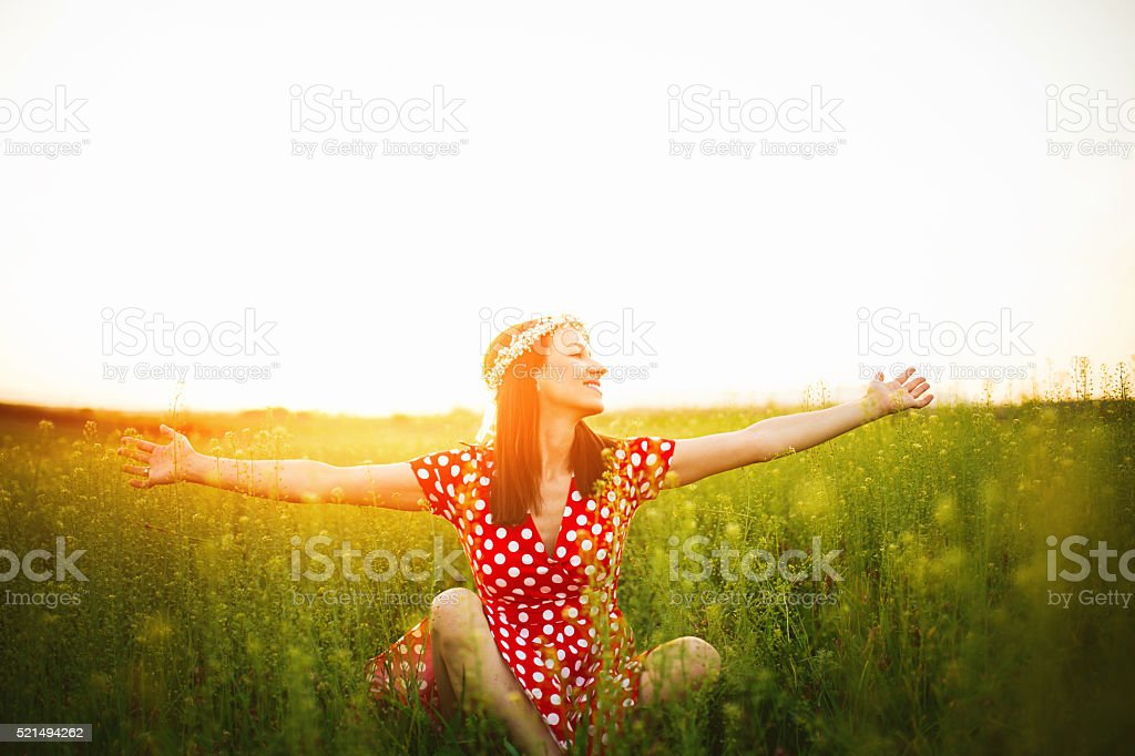 Girl is sitting on a meadow stock photo