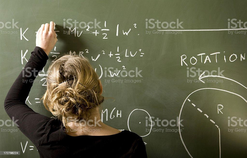Girl is solving a mathematical problem on blackboard stock photo