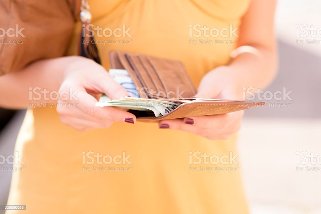 Girl is taking out money from wallet stock photo