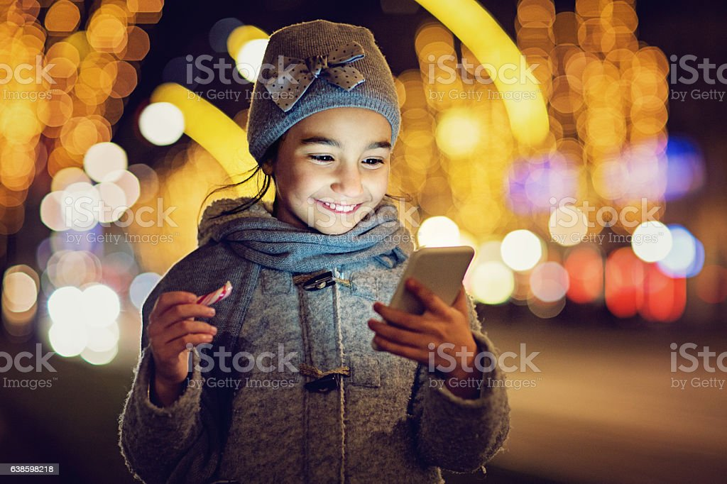 Girl is texting on the front of the Chrismas decoration stock photo