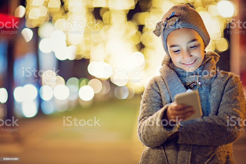 Girl is texting on the front of the city lights stock photo