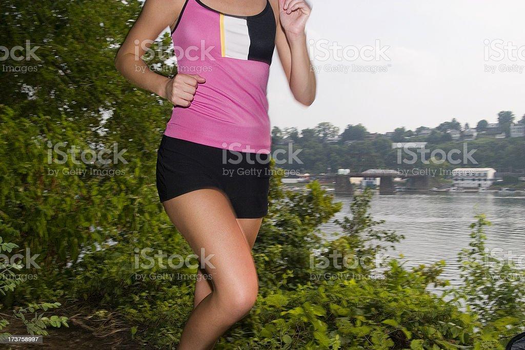Girl jogging along the river stock photo