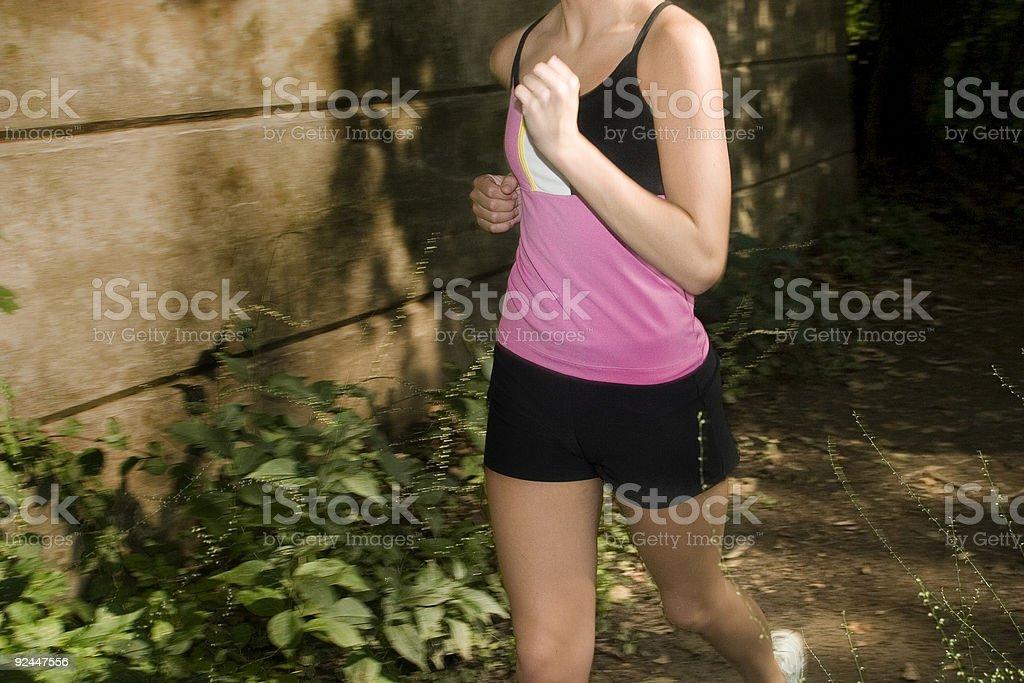 Girl jogging down trail stock photo