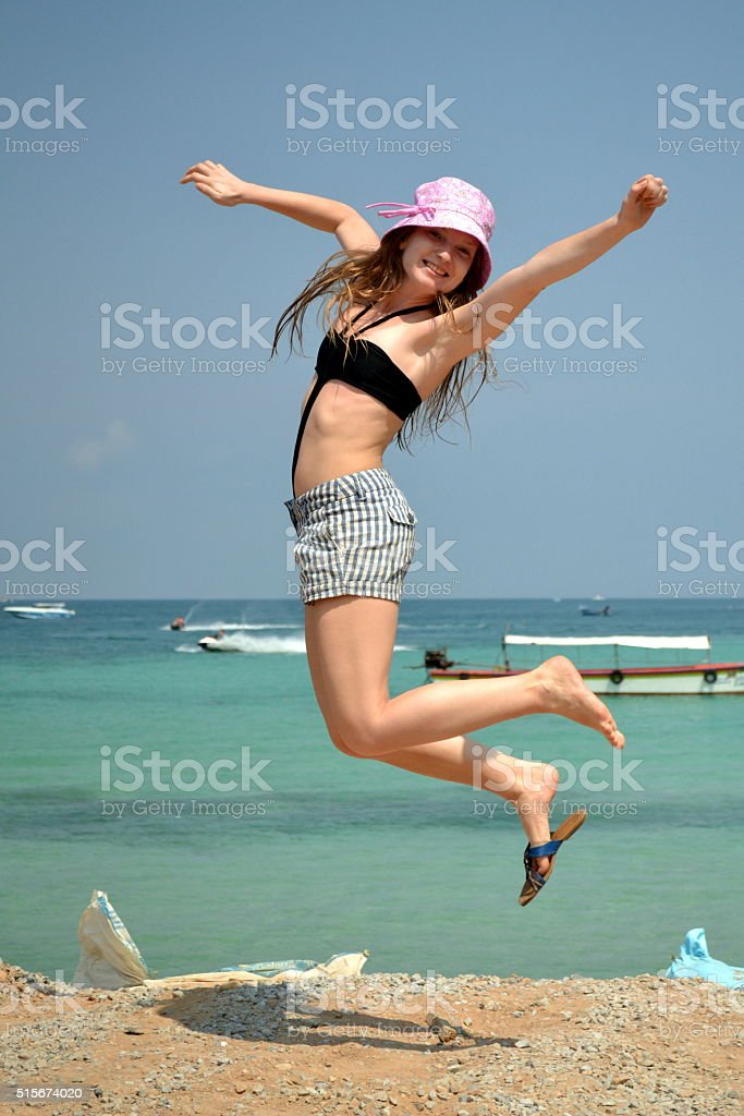 Girl jumping at the beach for positive emotion stock photo