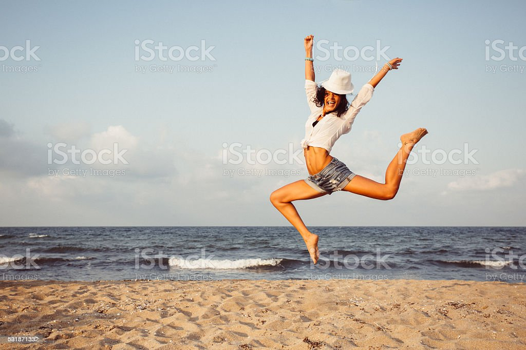 Girl jumping at the beach stock photo