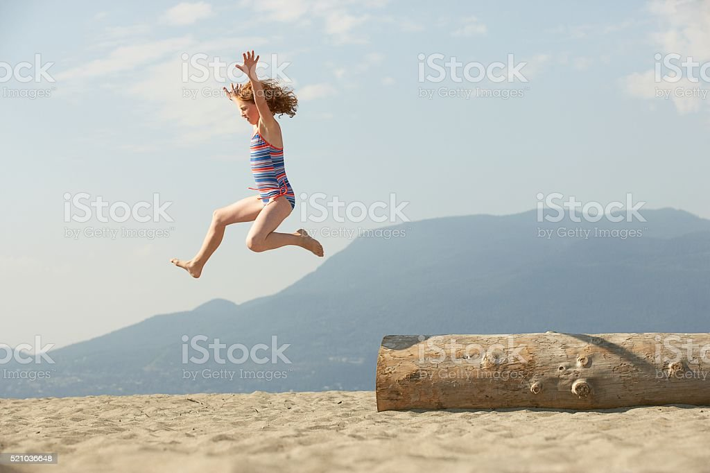 Girl jumping from a log on the beach stock photo