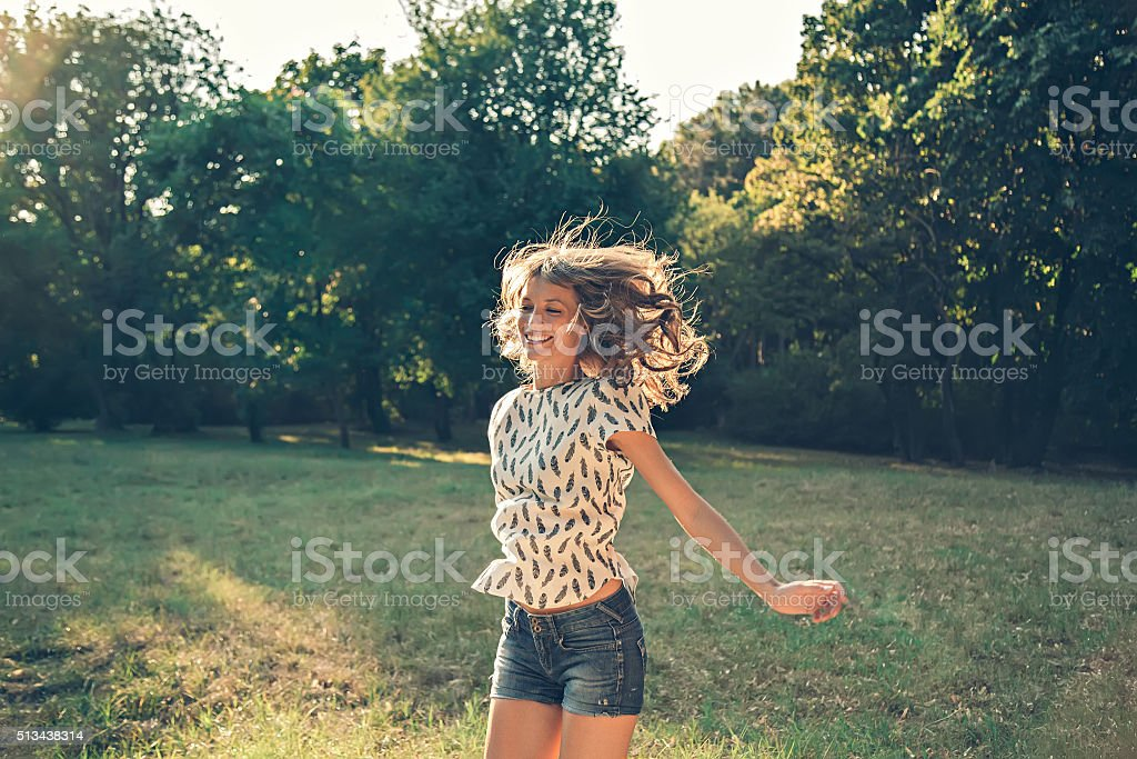 Girl jumping in a park stock photo
