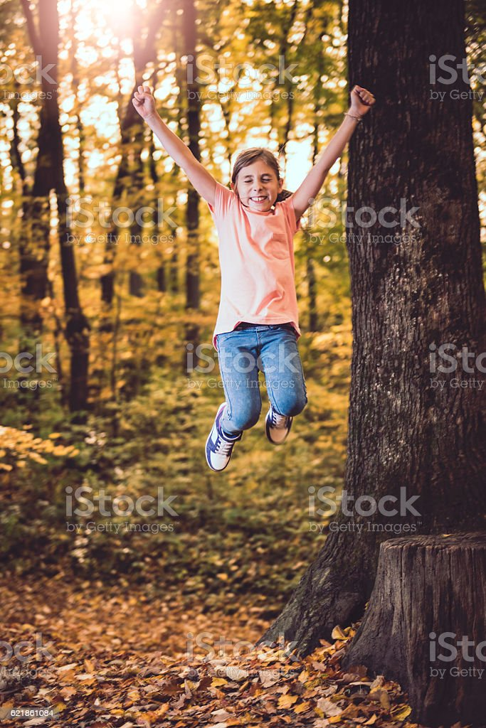 Girl jumping in the forest stock photo