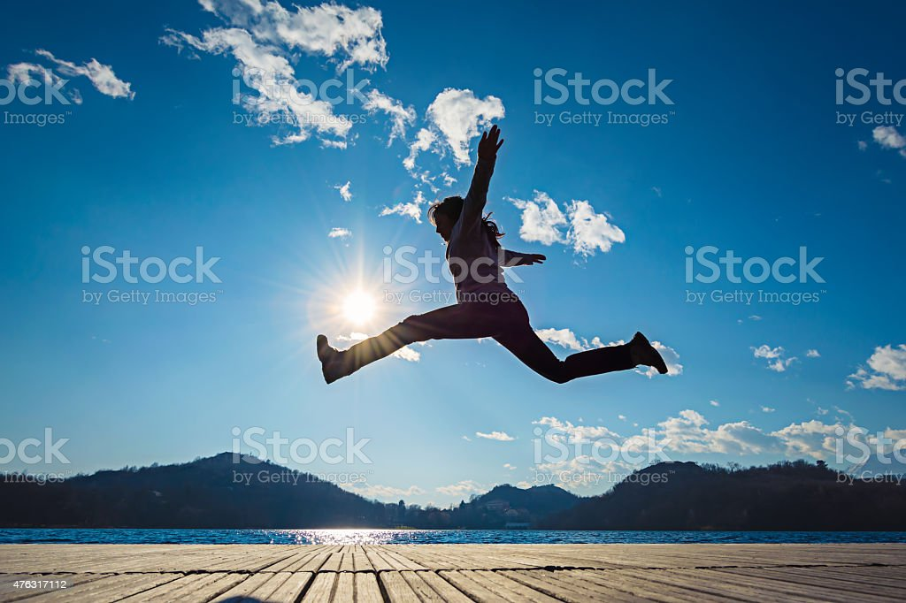 Girl jumping in the sun stock photo