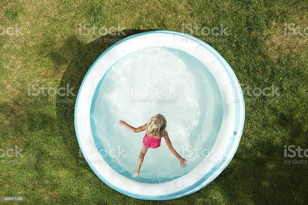 Girl Jumping into Inflatable Swimming Pool, Summer on Dried Grass stock photo