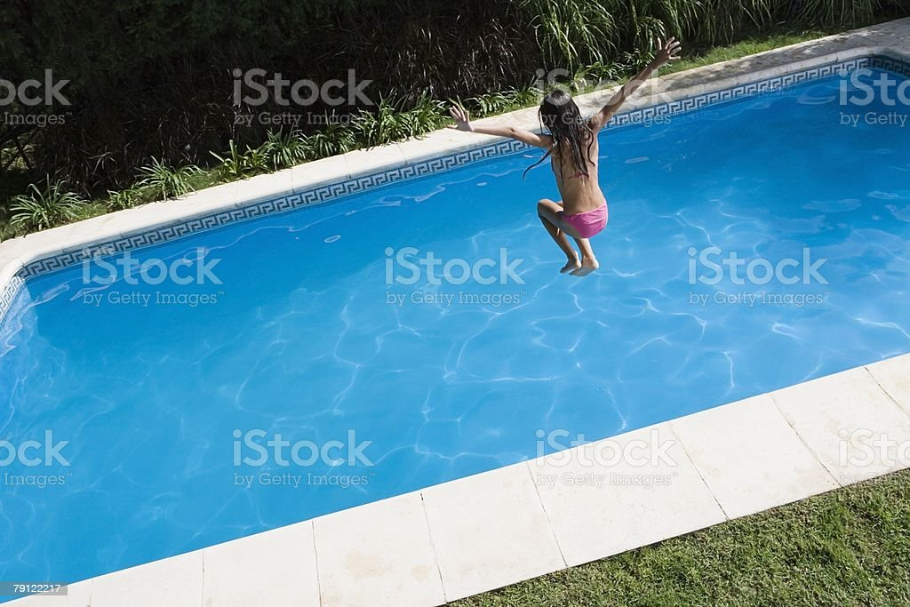 Girl jumping into swimming pool stock photo