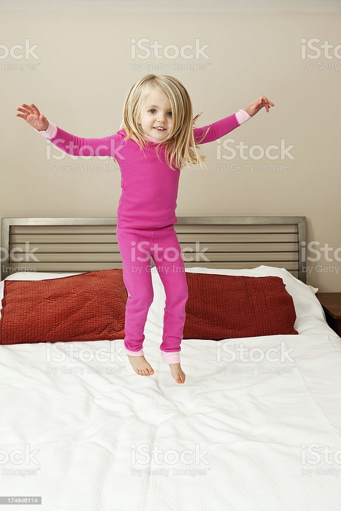 Girl Jumping on a Bed stock photo