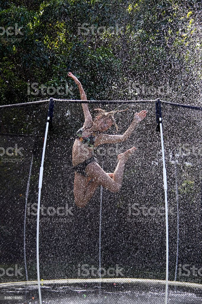 Girl Jumping on a Trampoline stock photo
