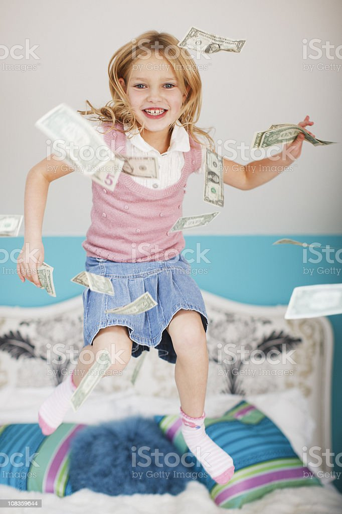 Girl jumping on bed with dollar bills royalty-free stock photo