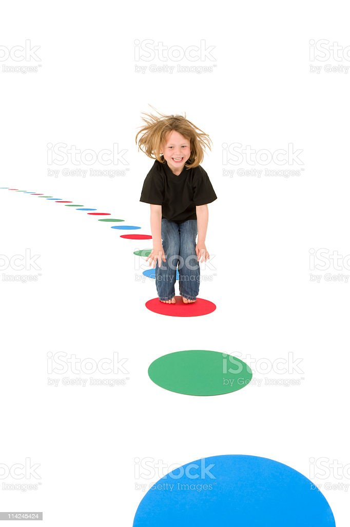 Girl jumping on colourful circles stock photo
