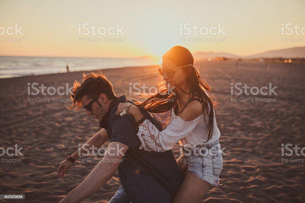 Girl jumping on her boyfriend back stock photo