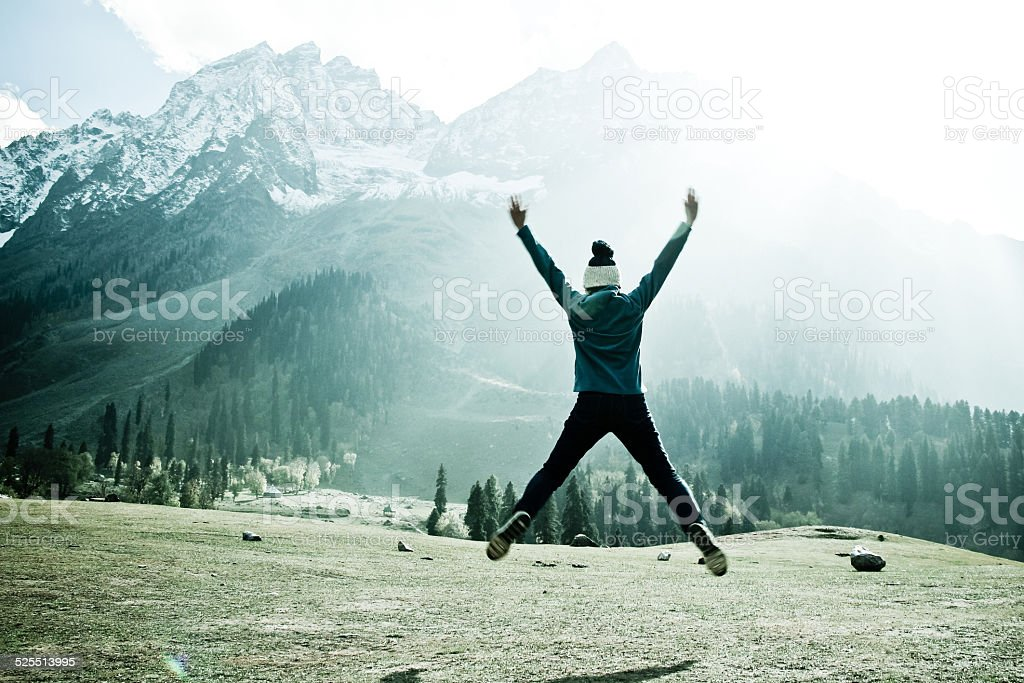 Girl jumping on meadow and iceberg view stock photo