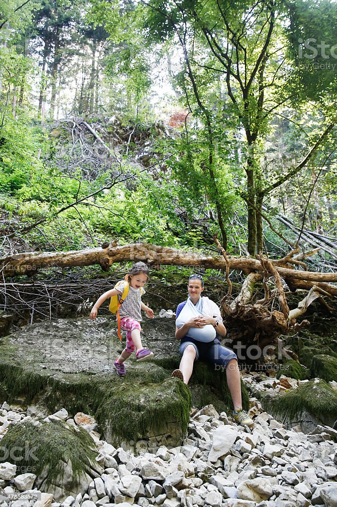 Girl jumping on stones, showing off to her mother stock photo