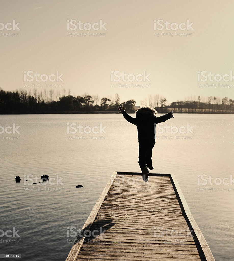 Girl Jumping on Wilderness Dock, Happiness Concept stock photo