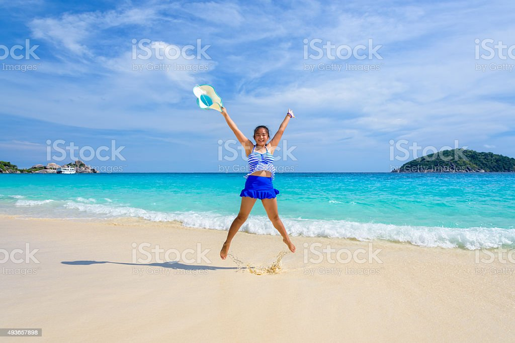 Girl jumping with happy on the beach at Thailand stock photo