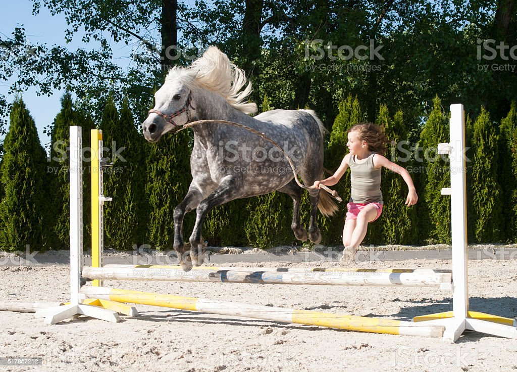 Girl jumping with pony stock photo