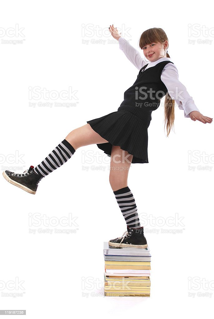 Girl jumps from a pile of books stock photo
