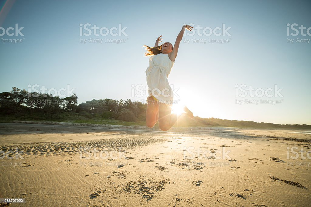 Girl jumps high up in the air on beach-sunset stock photo