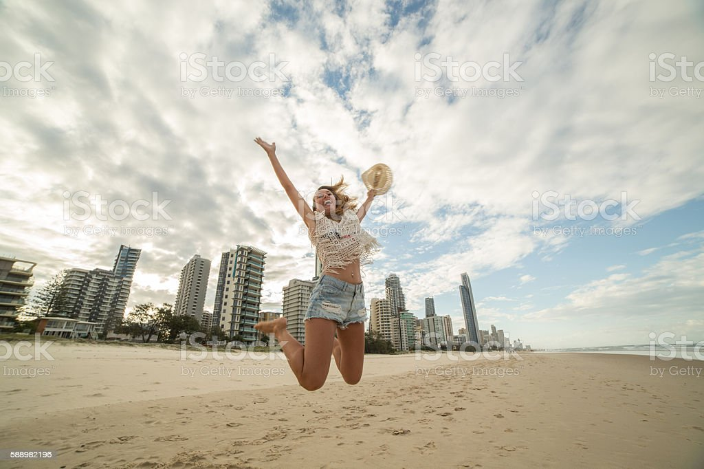 Girl jumps on beach high up in air stock photo