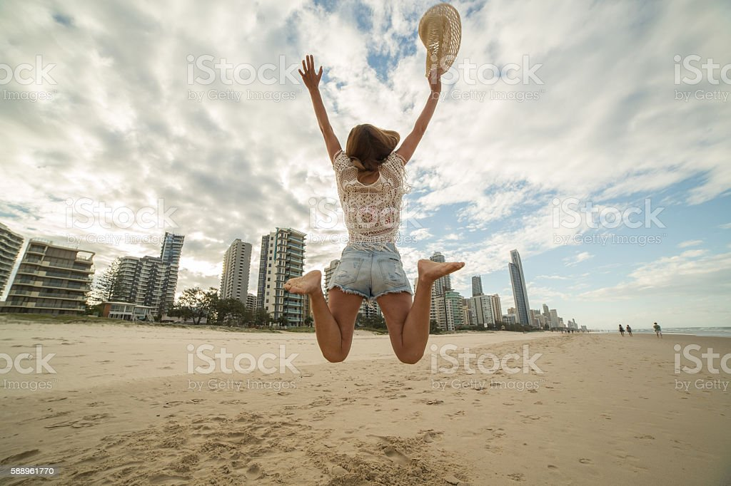Girl jumps on beach high up in air, Surfer's Paradise stock photo