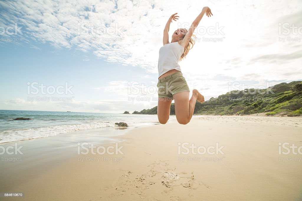 Girl jumps on beach high up in the air stock photo