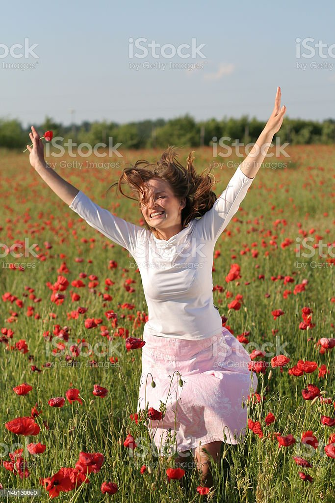 Girl jumps over poppy field royalty-free stock photo