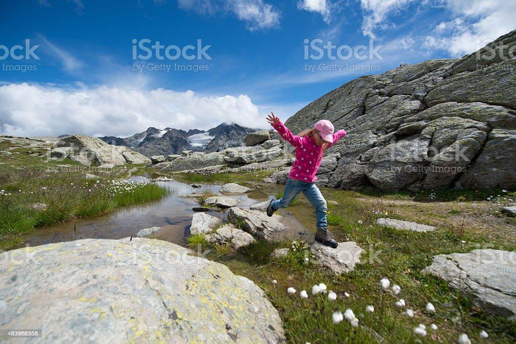 Girl jumps over rocks stock photo