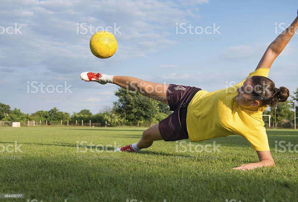 Girl kick soccer ball stock photo