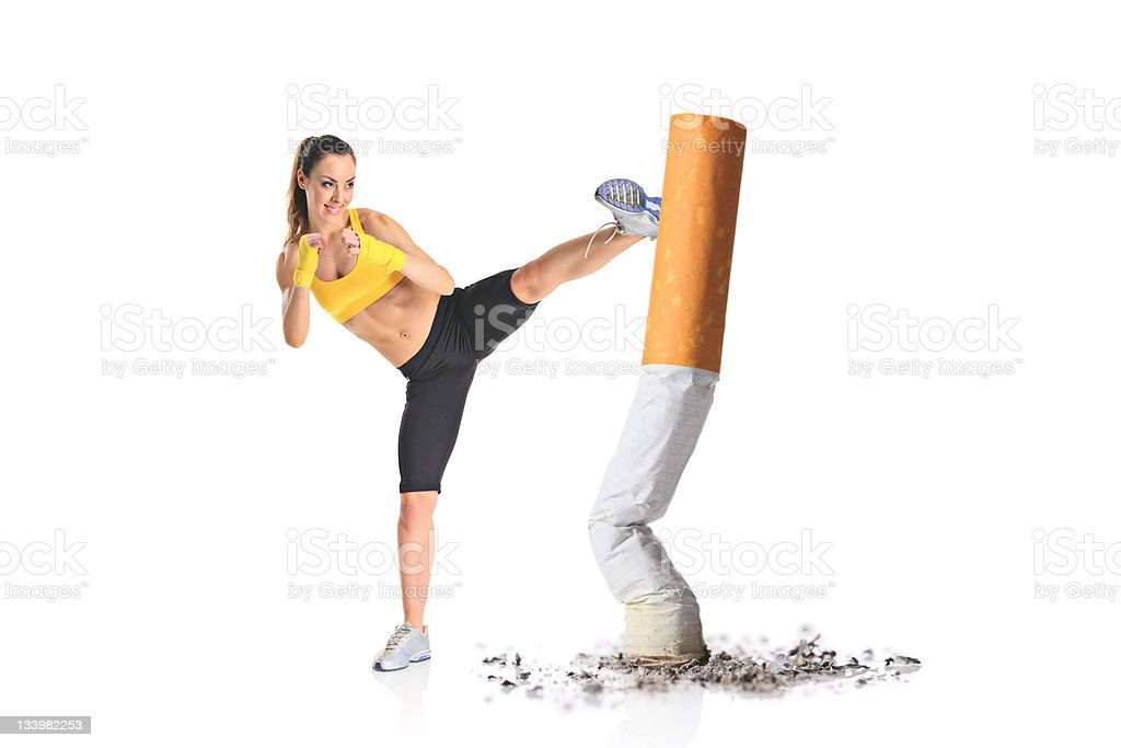 Girl kicking a cigarette butt stock photo