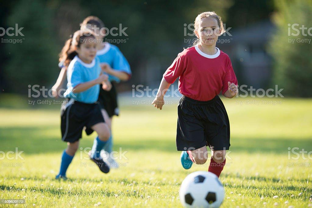 Girl Kicking a Soccer Ball stock photo