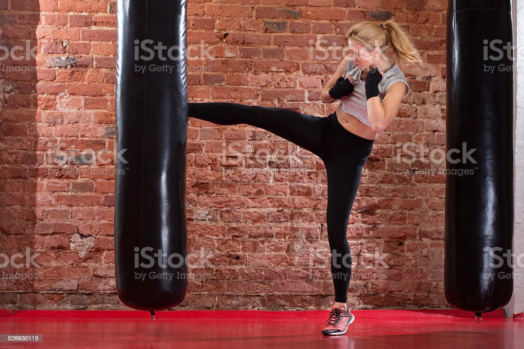 Girl kicking at punching bag stock photo