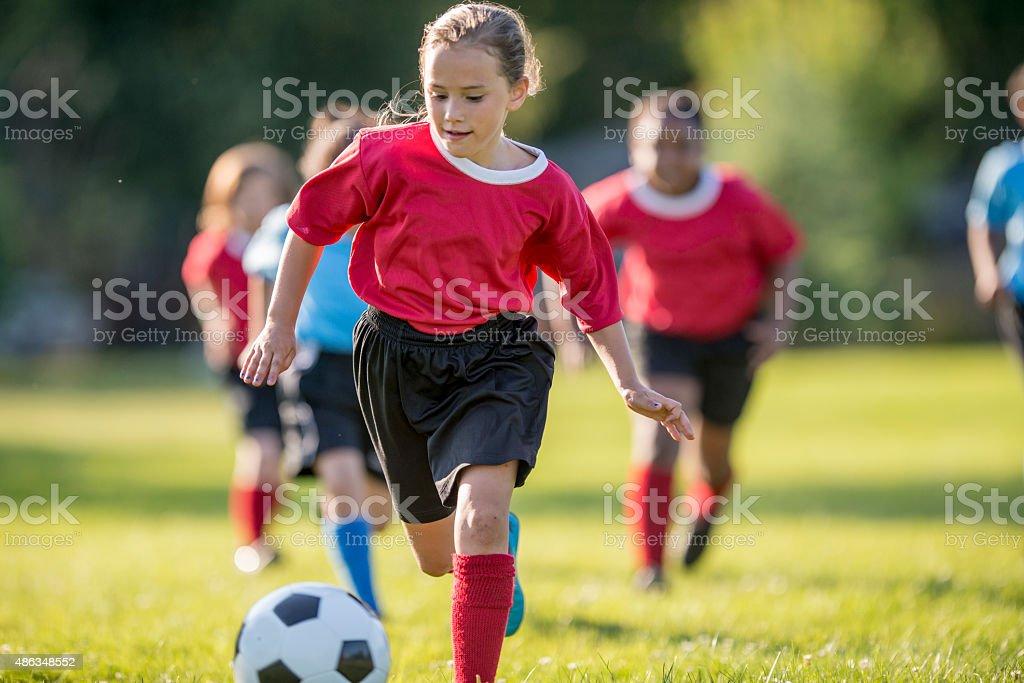 Girl Kicks Ball Up Field stock photo