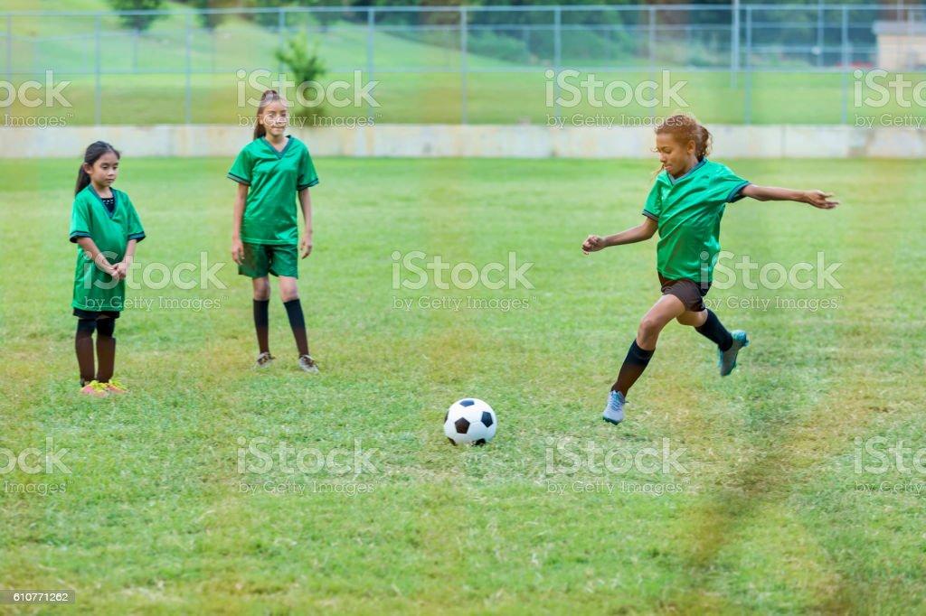 Girl kicks soccer ball during game stock photo