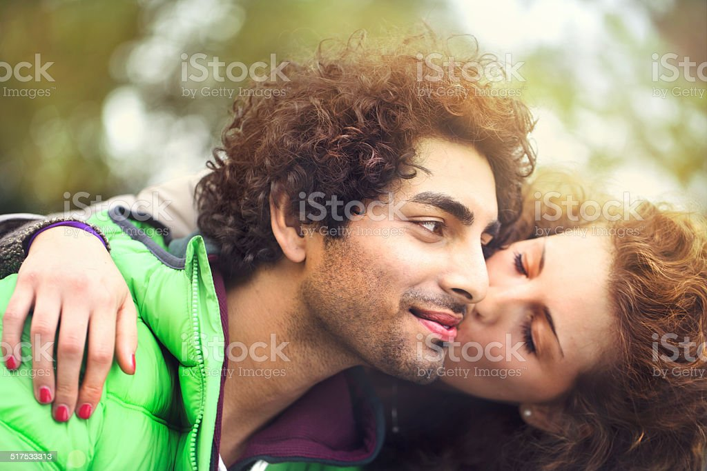 girl kissing and embracing her boyfriend around the city stock photo