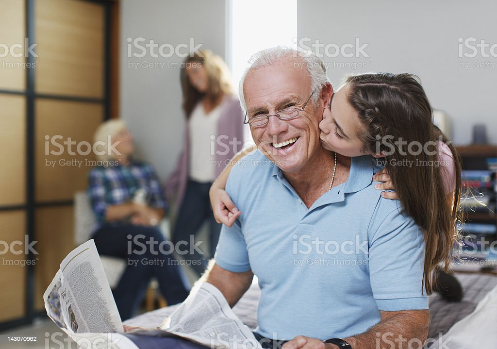 Girl kissing grandfather in home royalty-free stock photo