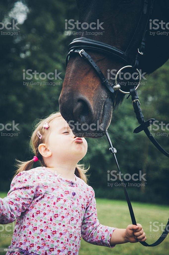 Girl kissing her horse stock photo