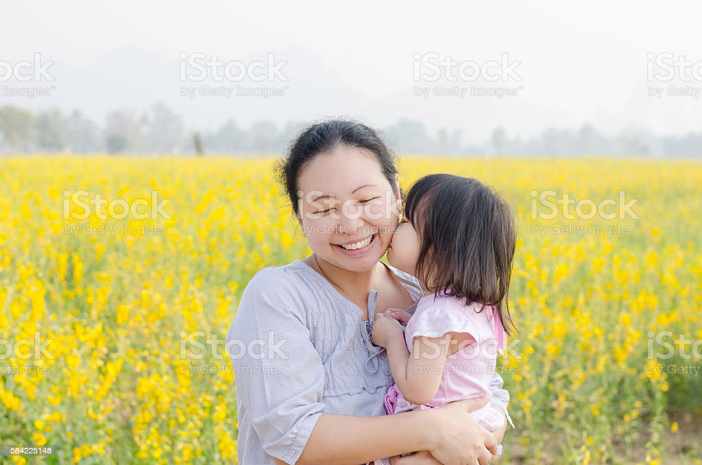 girl kissing her mom in flower field stock photo
