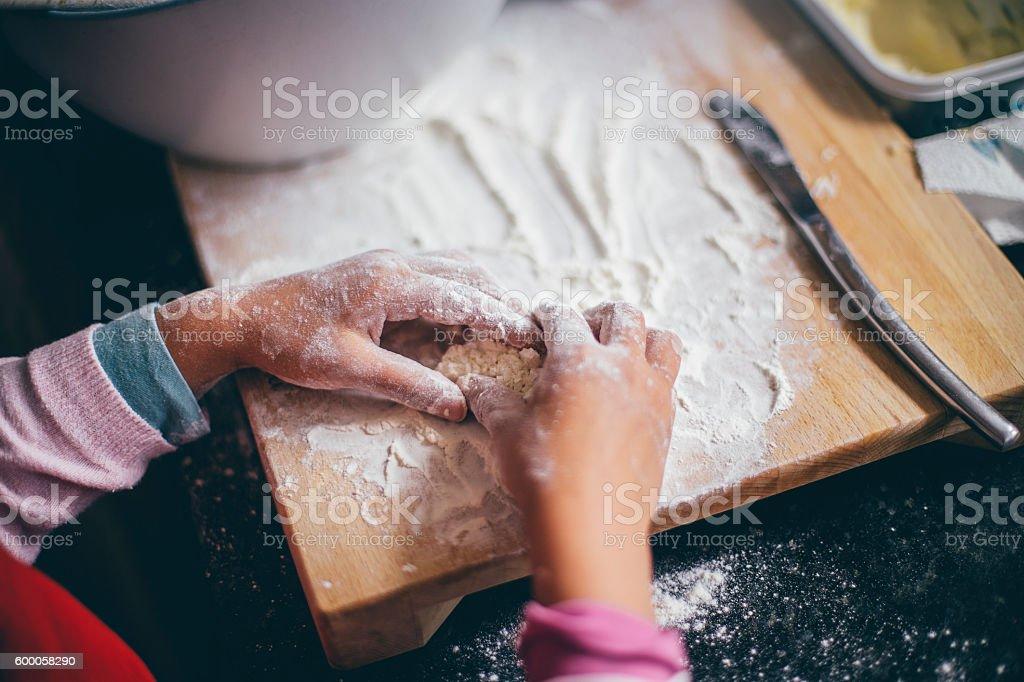 Girl Kneading Dough stock photo