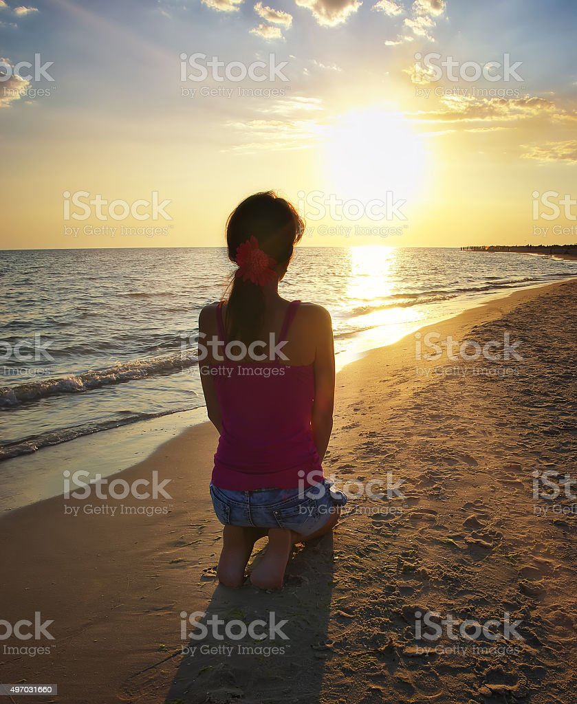 Girl kneeling on the beach stock photo