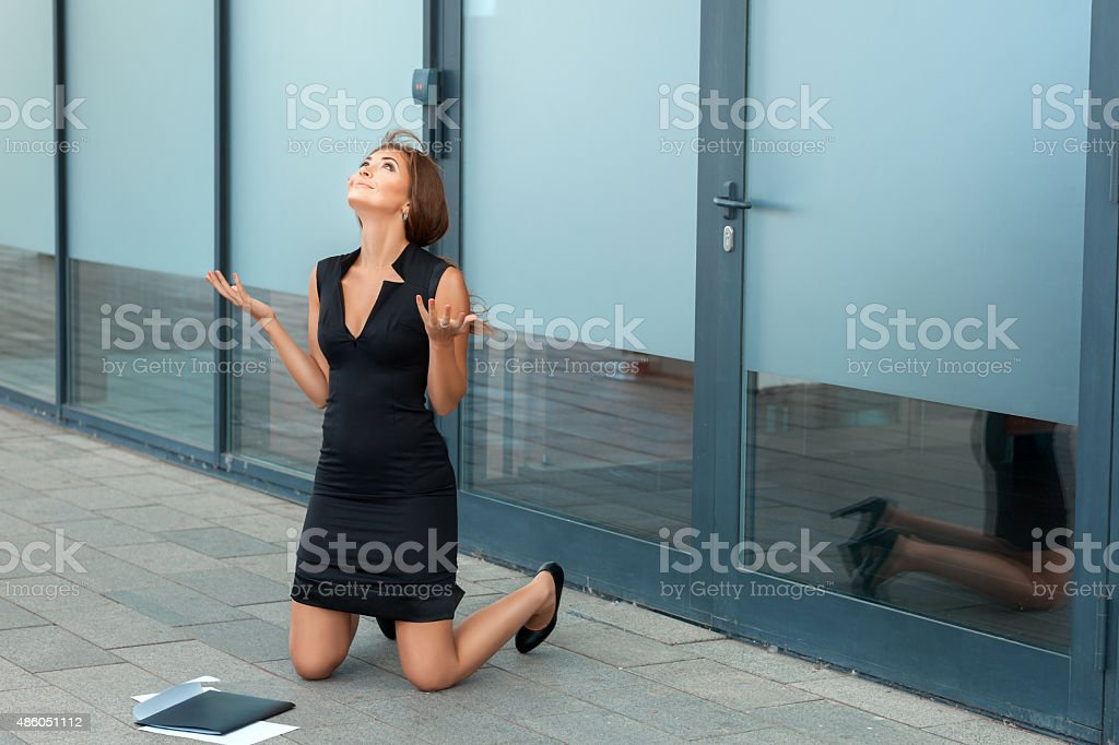 Girl kneels in front of the office. stock photo