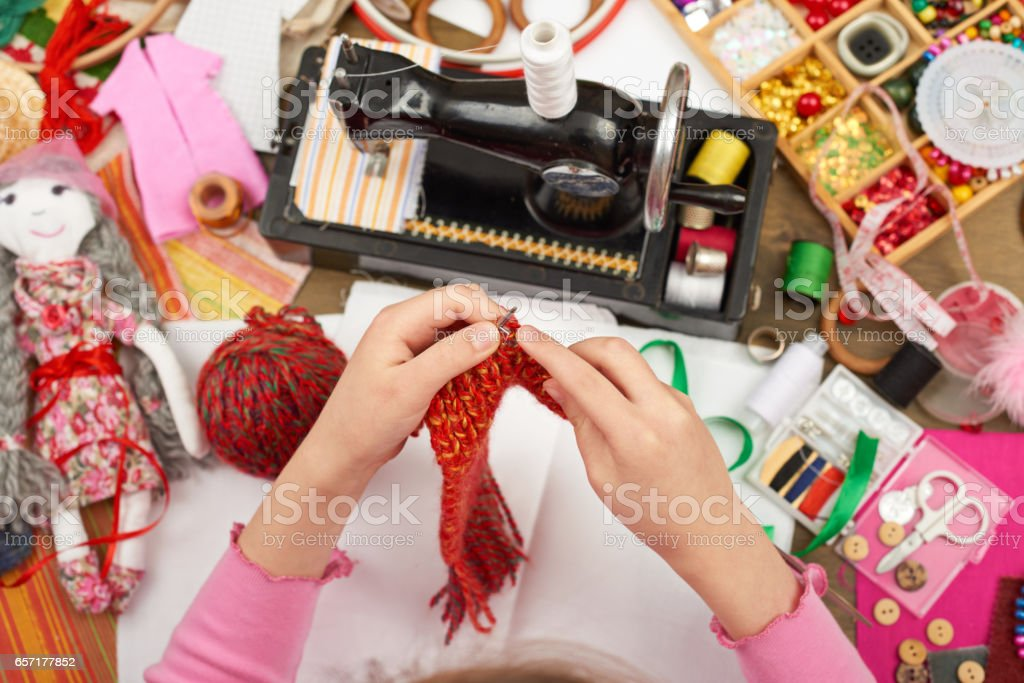 girl knit doll clothes, top view, sewing accessories top view, seamstress workplace, many object for needlework, handmade and handicraft stock photo