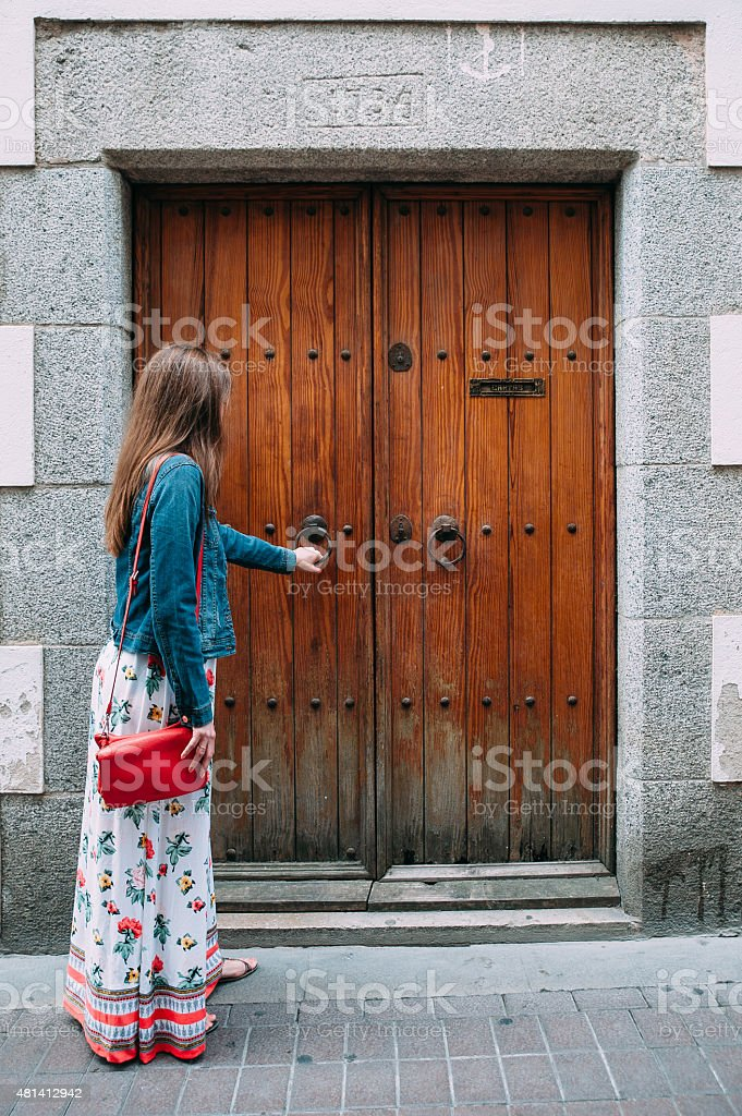 Girl knocking at the door stock photo